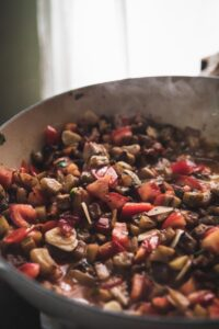 sauteed eggplant and diced tomatoes in a pan