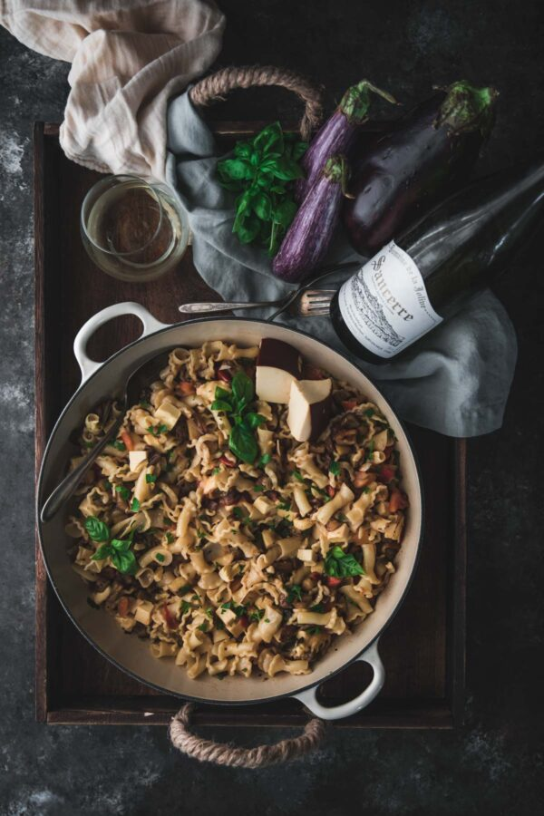 overhead of pasta in a large braiser with eggplants and a bottle wine on a tray