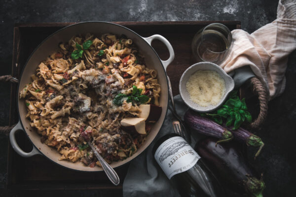 overhead shot of pasta in a braising dish on a tray with wine and cheese
