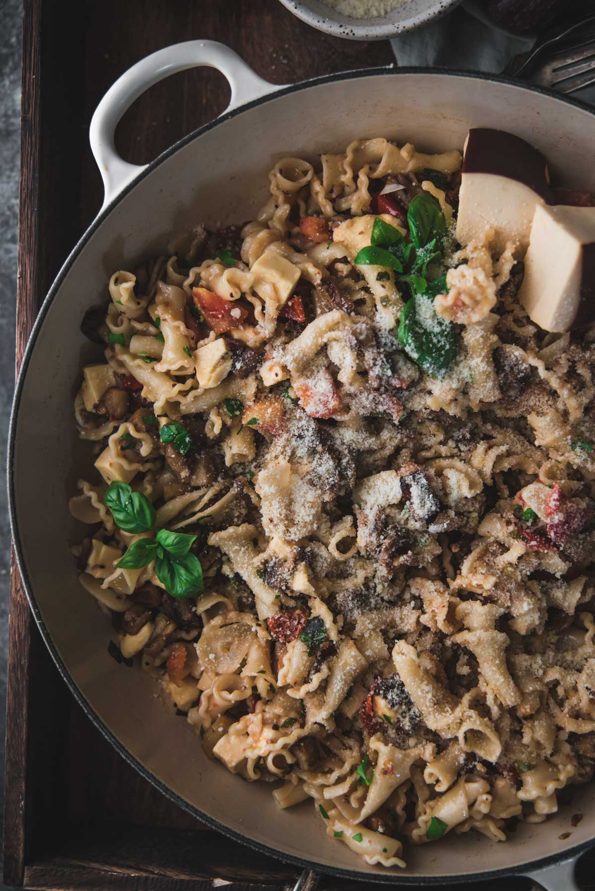overhead photo of pasta with sauteed eggplant and fresh diced tomatoes with smoked cheese