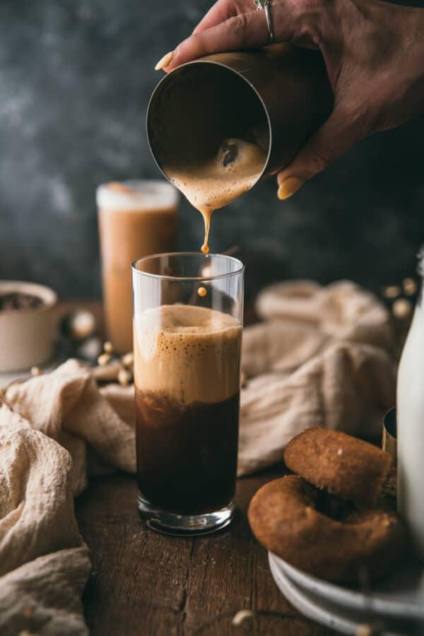 pouring foamy espresso into a glass