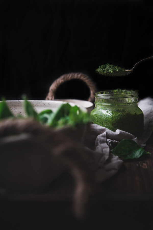 scooping green basil sauce out of a mason jar against a black background