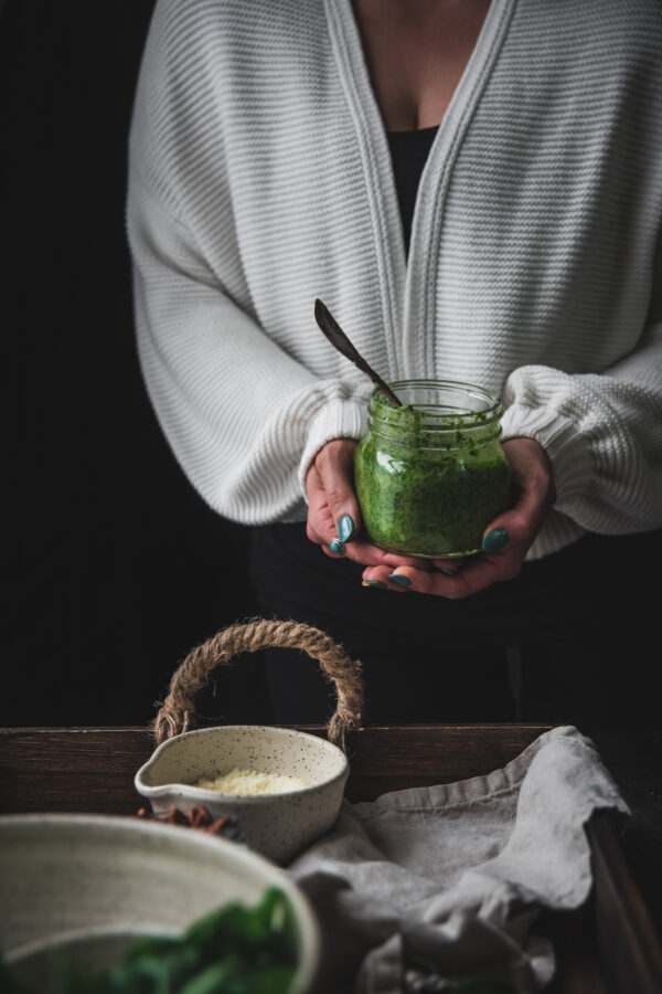 woman holding a jar of green sauce