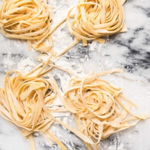 nests of homemade pasta on marble
