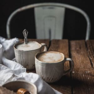 two mugs of foamy lattes on a wood surface