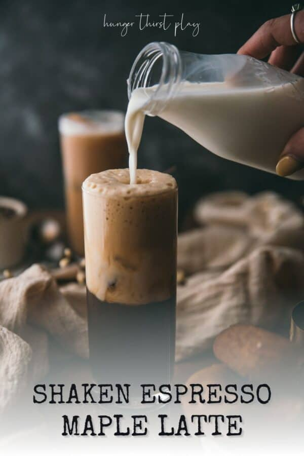 pouring milk into a glass with espresso