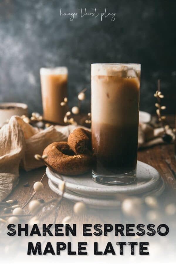 Layers of shaken espresso, ice, and milk in a glass on a plate with cider donuts
