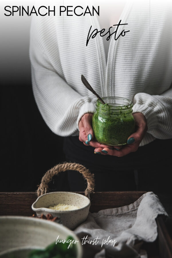 hands holding jar of pesto