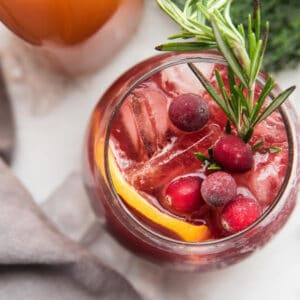 close up overhead of red sangria with cranberries and rosemary