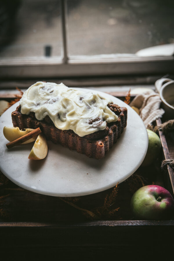 backlit side angle of apple bread with mascarpone glaze