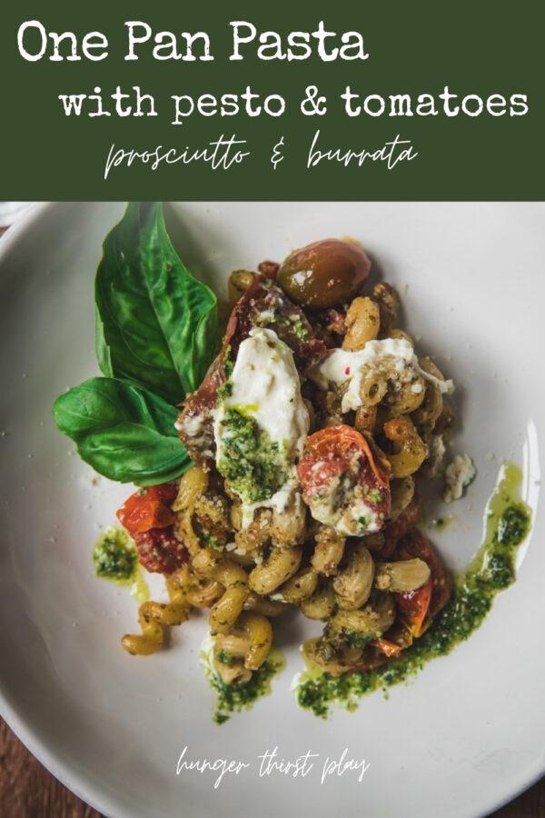 cavatappi pasta with pesto, tomatoes, and burrata on a plate